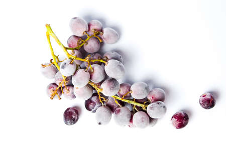 Frozen grapes cluster with ice on white background Imagens
