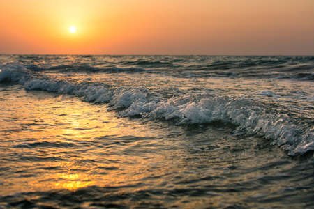 Calm sunset on the beach with small waves Stock Photo