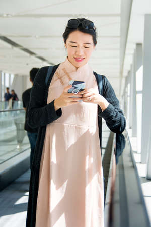 Girl using phone while on the moving walkway inside