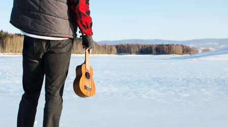 Man with ukulele standing on a frozen lake