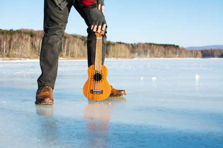 Man with ukelele standing on a frozen lake  Stock Photo