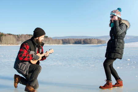 Man playing ukelele for his girlfriend on a frozen lake