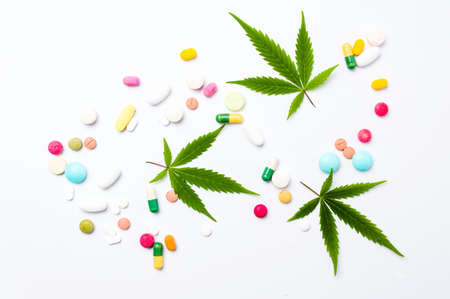 Marijuana leaf and colorful medical pills on white