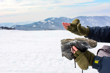 Man removing snow from his shoe on a winter hiking trip