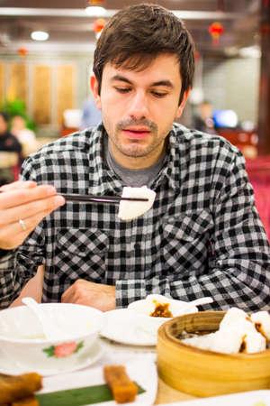 Foreigner enjoying Chinese food in restaurant