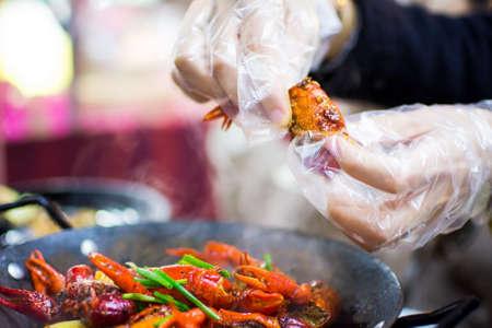 Mani con guanti di plastica prendendo gamberi dal piatto di gamberi piccante sul tavolo