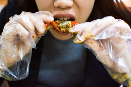 Asian woman eating a crayfish with plastic gloves Stock Photo