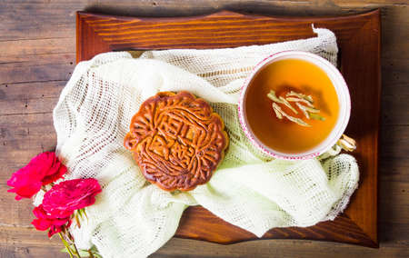 Chinese mooncake and tea with rose served on wooden saucer