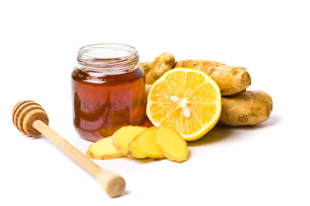 Jar of honey and lemon, gingers isolated on white background.