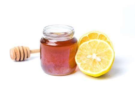 Jar of honey and lemon isolated on white background. Stock Photo