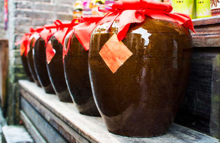 Homemade Chinese wine fermented with osmanthus flowers packed in traditional vats