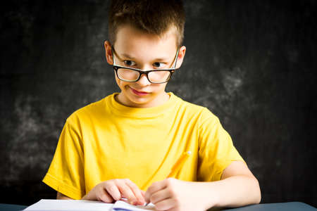 Boy making faces while studying for homework Stock Photo