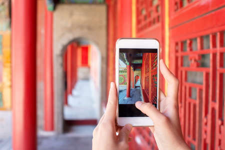 Tourist taking picture in the Forbidden city with a smartphone