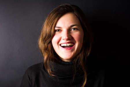 Happy brunette in black sweater smiling portrait on dark background