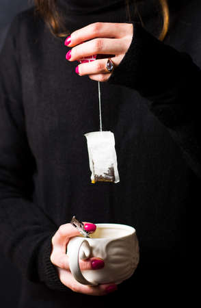 Female hands taking out teabag close up Stock Photo