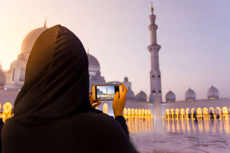 Female tourist taking picture of Sheikh Zayed Grand Mosque by phone Stock Photo
