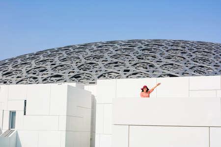 ABU DHABI, VEREINIGTE ARABISCHE EMIRATE - 26. JANUAR 2018: Glücklicher Tourist im Louvre Abu Dhabi-Gebäude an einem sonnigen Tag