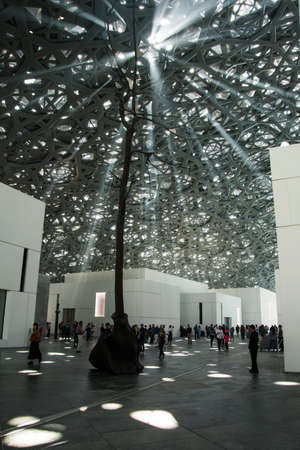 ABU DHABI, VEREINIGTE ARABISCHE EMIRATE - 26. JANUAR 2018: Lichter, die durch Dach und Decke des Louvre Abu Dhabi gehen, das Regen des Lichtdesignmerkmals darstellend