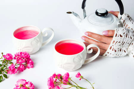 Female hands on a teapot. Rose tea time Stock Photo