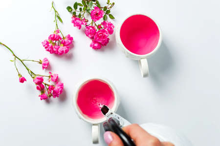 Person pouring tea with rose flowers on white table