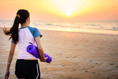 Girl with yoga mat on the beach for outdoors workout Stock Photo