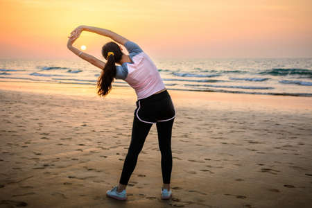 Girl exercising on the beach at sunset, outdoors workout