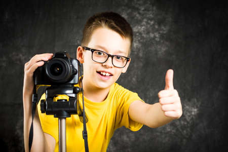 Teenage boy learning how to use a big digital camera