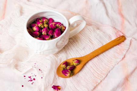 Rose tea buds in a white tea cup Foto de archivo