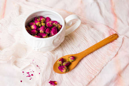 Rose tea buds in a white tea cup Standard-Bild