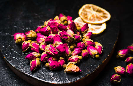 Rose tea buds and lemon slices on dark plate Фото со стока