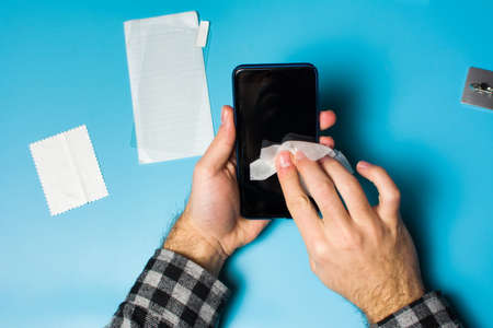 Man cleaning phone screen to apply protective tempered glass Stok Fotoğraf - 96075857