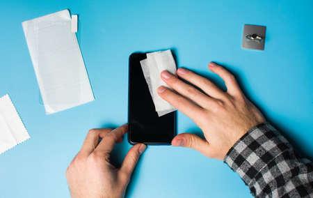 Man schoonmaak telefoonscherm om beschermend gehard glas aan te brengen