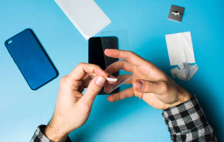 Man applying protective tempered glass to smart phone screen Foto de archivo