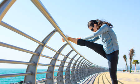 Girl stretching before workout by the seaside. Active lifestyle