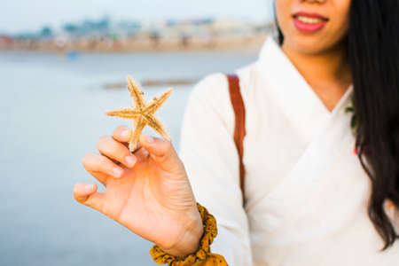 843f9b564b8 Female holding a starfish on the beach at sunset