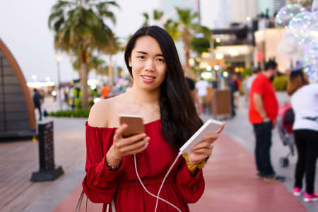 Girl using phone while charging on the power bank outdoors Imagens