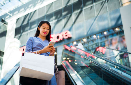 Girl using phone while on moving stairs in the mall Stock Photo