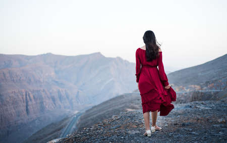 Fashionable girl on a desert mountain top wearing red dress
