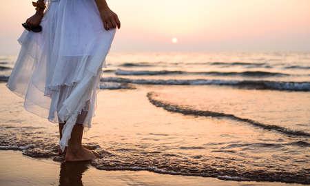 Girl walking on the beach wearing white dress at sunset
