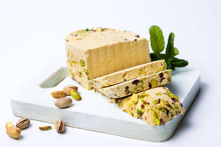 Halva with pistachio on a cutting board isolated on white