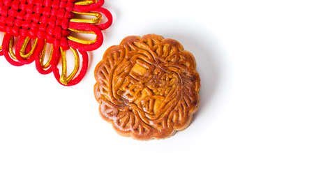 Traditional homemade moon cake and Chinese knot on white background