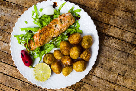 Salmon steak with young potato served on a plate