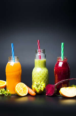Various fruit smoothies in glasses against dark background