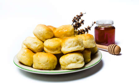 Homemade pastry buns with honey on a plate