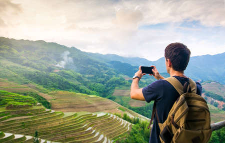 Man taking picture of stunning Asian rice terrace landscape view