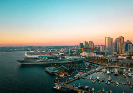 San Diego bay area with high buildings, cruisers and an aircraft carrier aerial