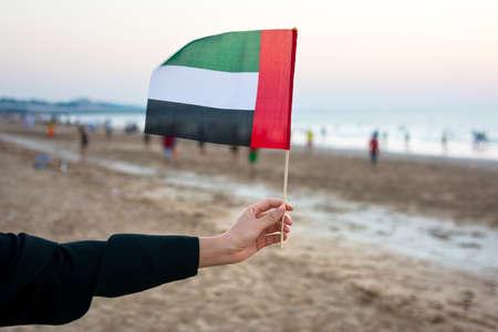 Female hand holding United Arab Emirates flag on the beach