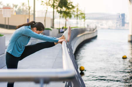 Girl stretching with music before running in urban environment