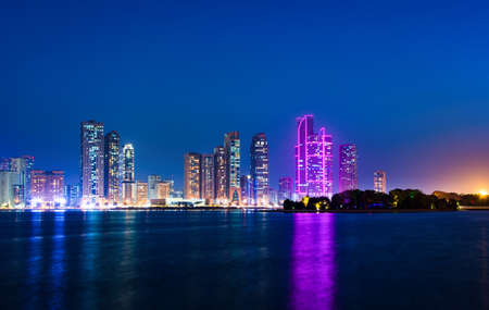 Sharjah modern waterfront cityscape in UAE at blue hour