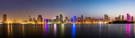 Full panoramic view of Sharjah waterfront cityscape in UAE at dusk Stock Photo